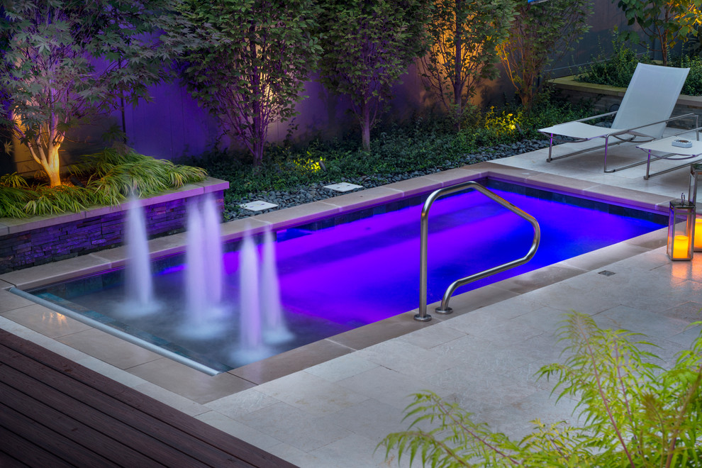 Example of a small classic courtyard stone and rectangular lap pool fountain design in Chicago