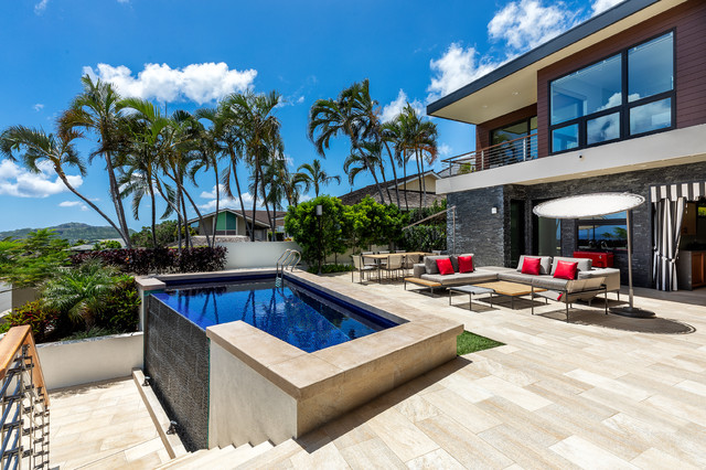 Inspiration for a mid-sized modern backyard tile and custom-shaped infinity pool remodel in Hawaii