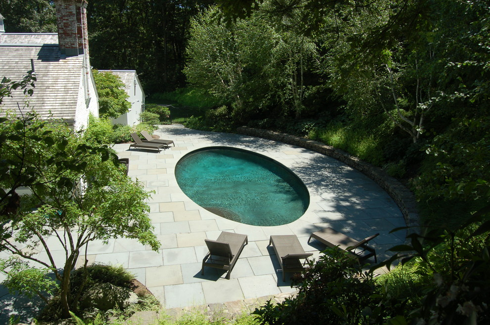 Inspiration for a mid-sized timeless backyard round and stone pool remodel in Boston