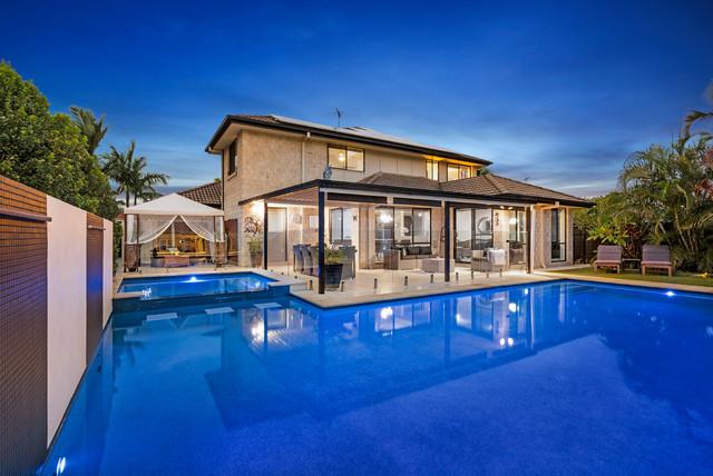 Ejemplo de piscinas y jacuzzis naturales, actuales, grandes, a medida, en patio trasero, con adoquines de piedra natural