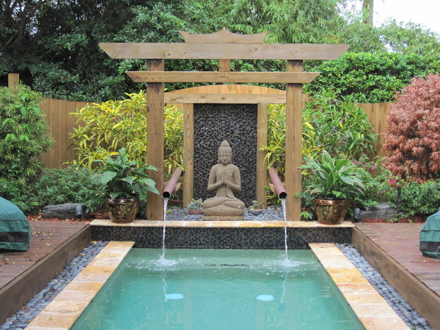 Inspiration for an asian rectangular pool in Miami with decking and a water feature.