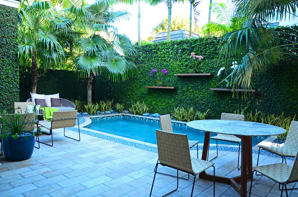 Example of a mid-sized trendy backyard rectangular and tile pool design in Miami