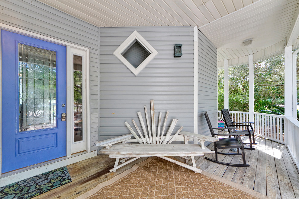 Inspiration for a coastal front porch remodel in Miami with decking and a roof extension