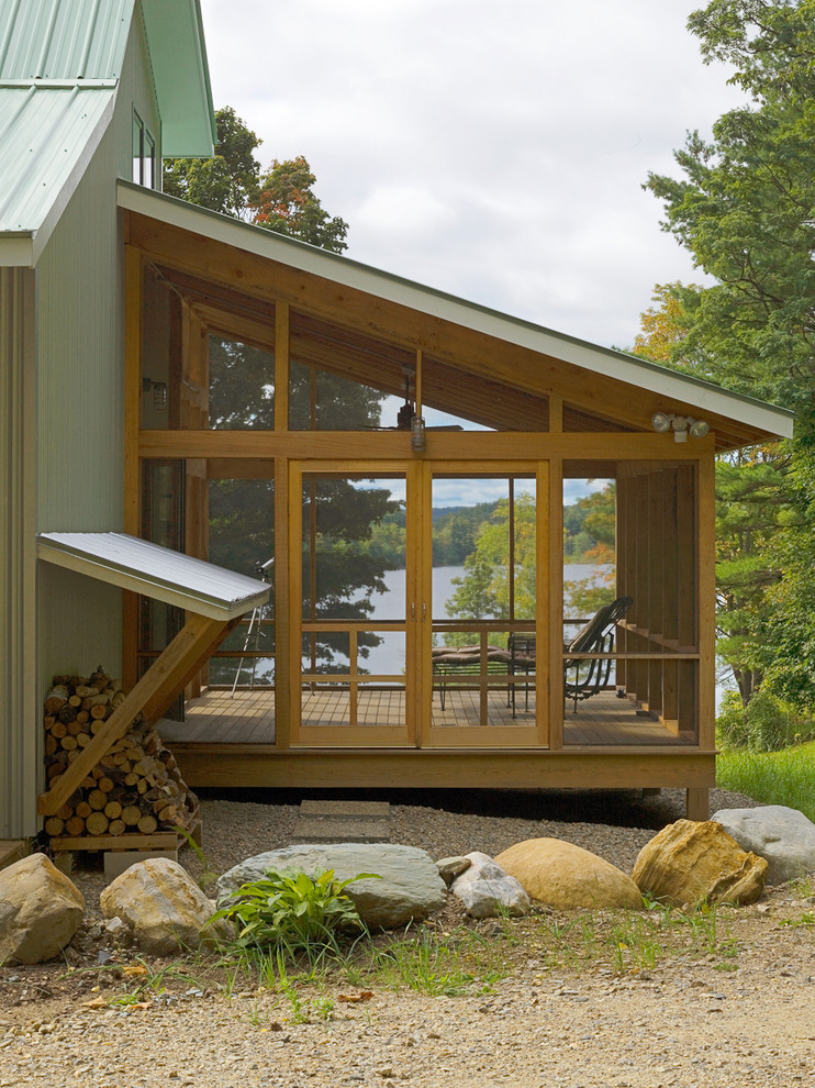 This is an example of a rustic screened-in porch design in Burlington with decking and a roof extension.