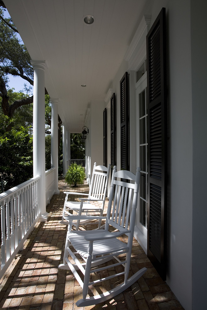 This is an example of a traditional brick porch design in Miami with a roof extension.