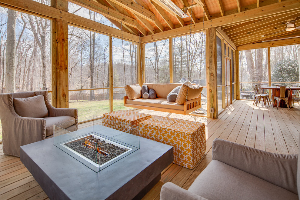 This is an example of a huge country screened-in back porch design in DC Metro with decking and a roof extension.