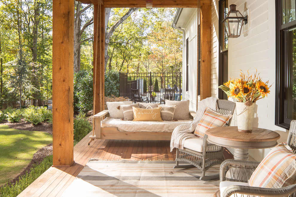 This is an example of a huge farmhouse front porch design in Atlanta with decking and a roof extension.
