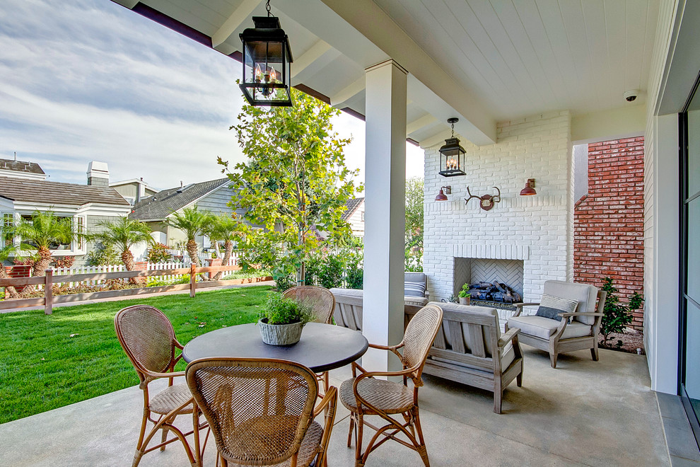 Mid-sized farmhouse concrete paver front porch photo in Orange County with a fireplace and a roof extension