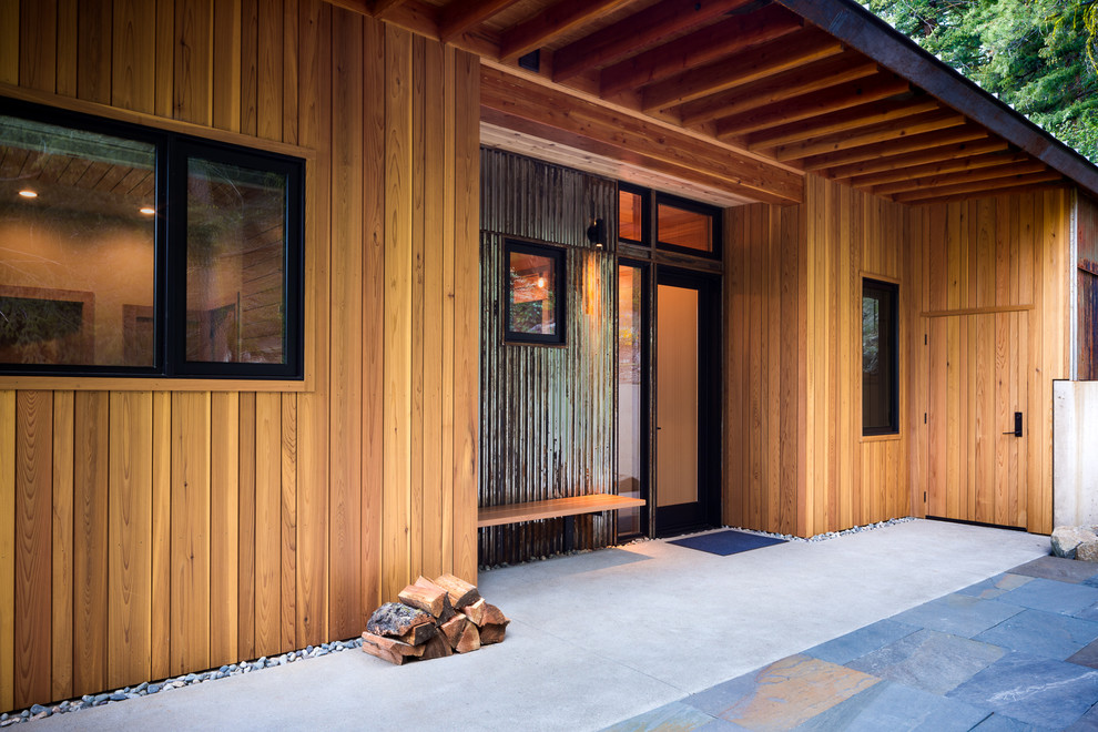Inspiration for a mid-sized rustic concrete front porch remodel in Seattle with a roof extension