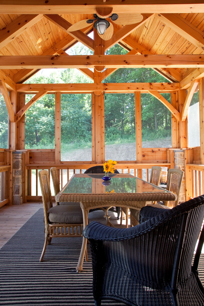 This is an example of a rustic screened-in porch design in Baltimore with decking and a roof extension.