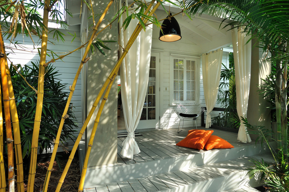 Island style porch idea in Miami with decking and a roof extension