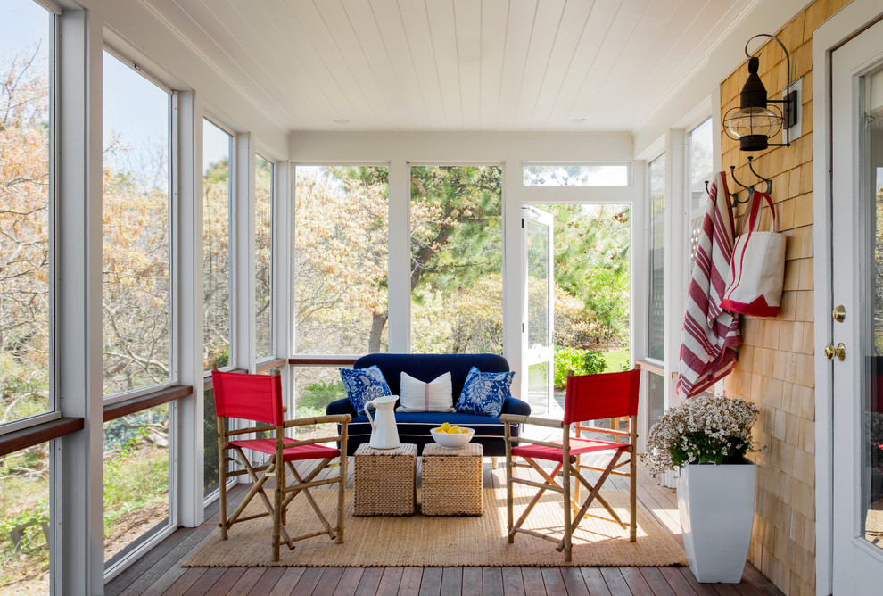 Inspiration for a mid-sized coastal screened-in porch remodel in Boston with decking and a roof extension