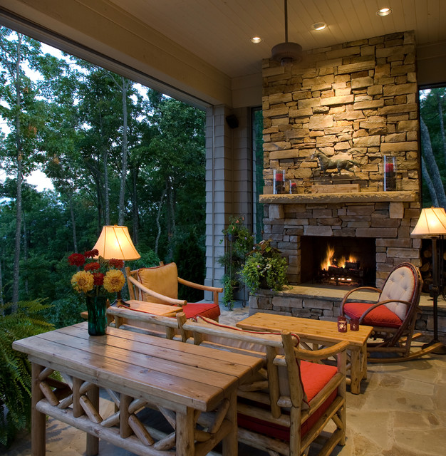 Inspiration for a rustic stone porch remodel in Other with a fire pit