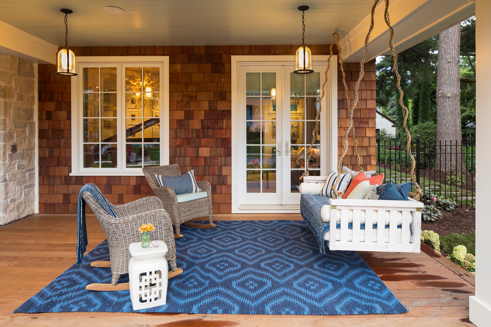 Large beach style front porch idea in Minneapolis with a roof extension