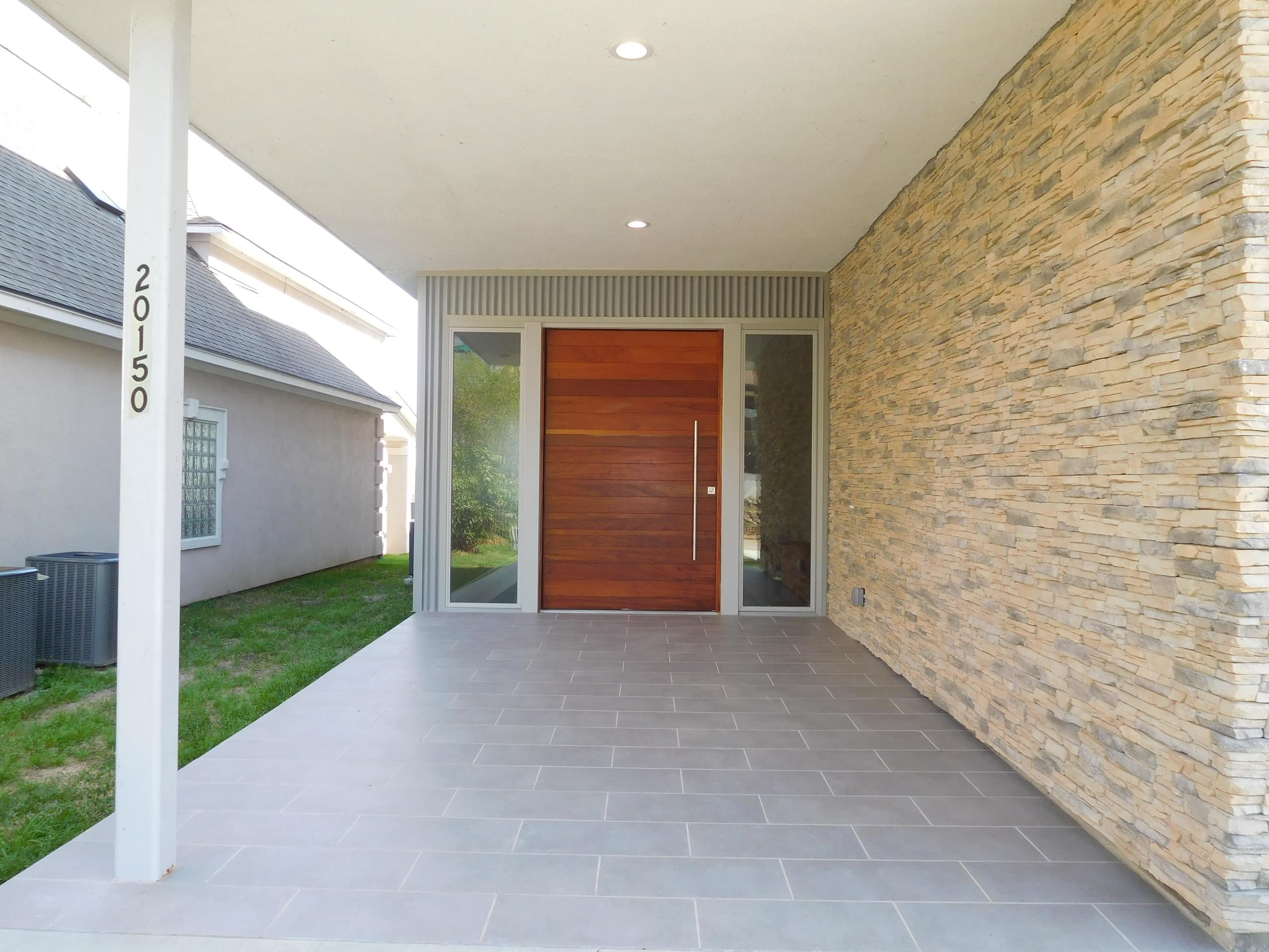 Covered entry with large pivot door