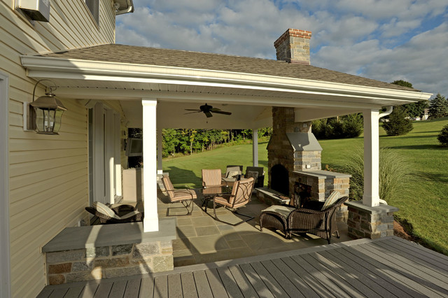 covered porch with stone hearth fireplace and attached deck