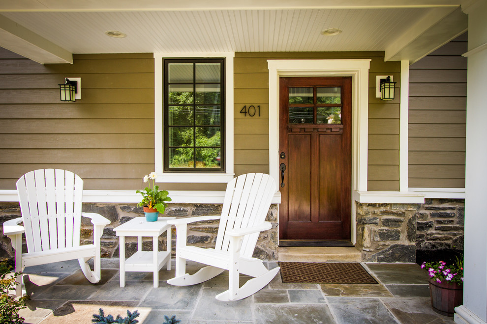 Mid-sized elegant stone front porch photo in Philadelphia with a roof extension