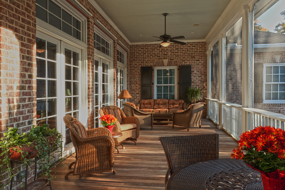 This is an example of a traditional screened-in back porch design in Charleston with decking and a roof extension.