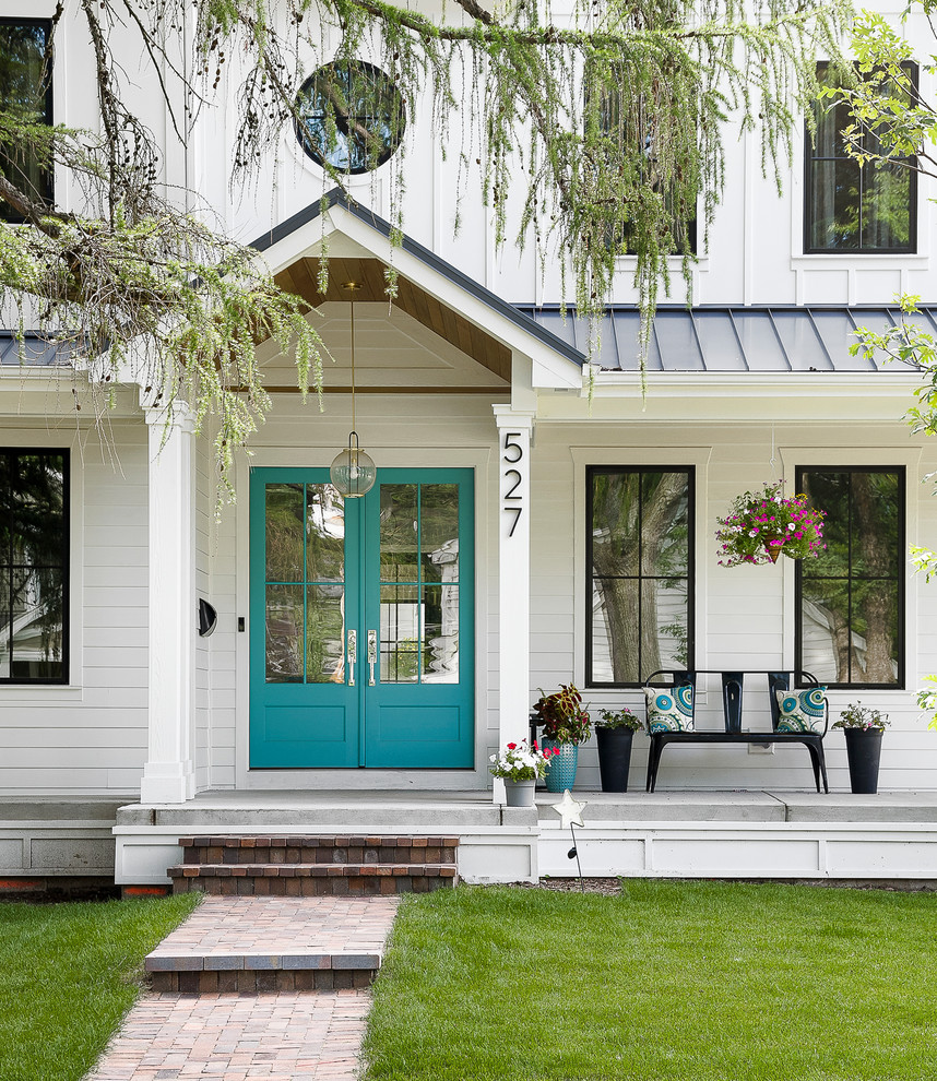 This is an example of a country concrete porch container garden design in Chicago with a roof extension.