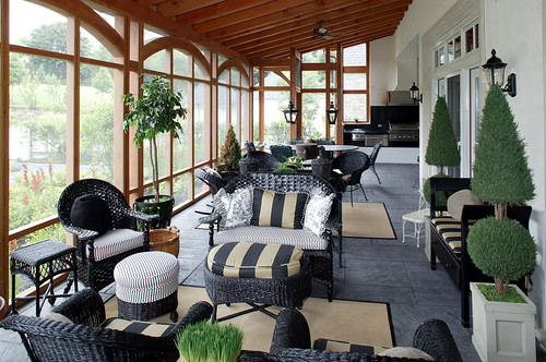 An elegant porch featuring topiary trees, wicker seats, cushions, ottomans, and wide glass windows