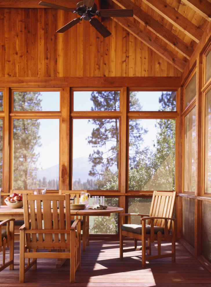 This is an example of a rustic screened-in porch design in San Francisco with decking and a roof extension.