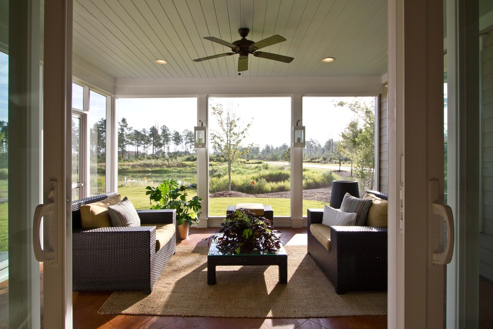 This is an example of a large traditional tile screened-in back porch design in Other with a roof extension.