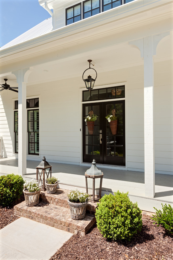 This is an example of a cottage front porch design in Atlanta.