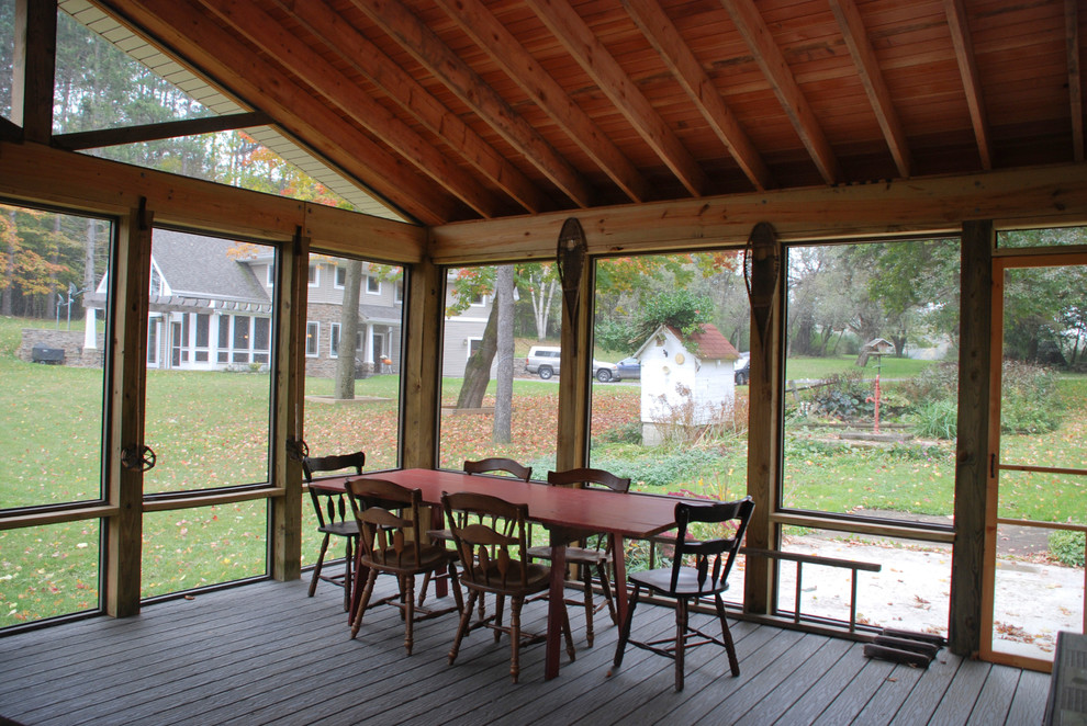 Inspiration for a large cottage screened-in side porch remodel in New York with decking and a roof extension