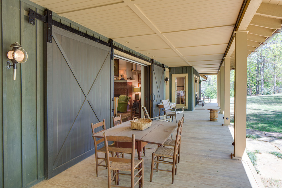 Large country front porch idea in Nashville with decking and a roof extension