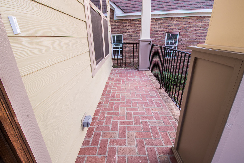Inspiration for a small timeless brick front porch remodel in Other with a roof extension