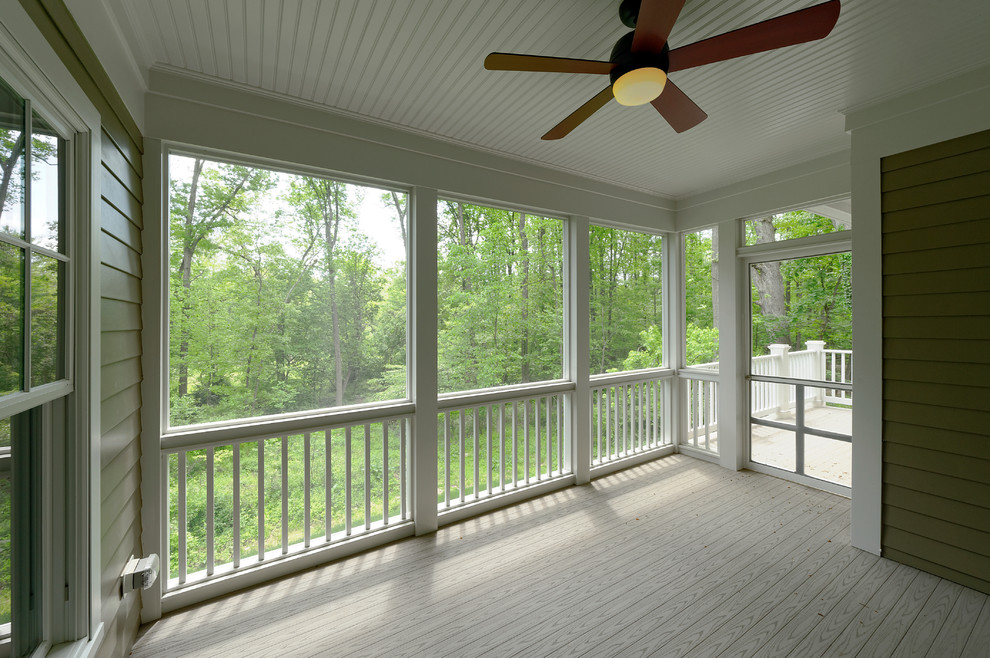 This is an example of a mid-sized craftsman screened-in back porch design in DC Metro with a roof extension and decking.