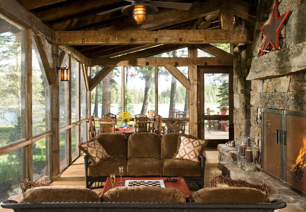 Mountain style screened-in porch idea in Denver with decking and a roof extension