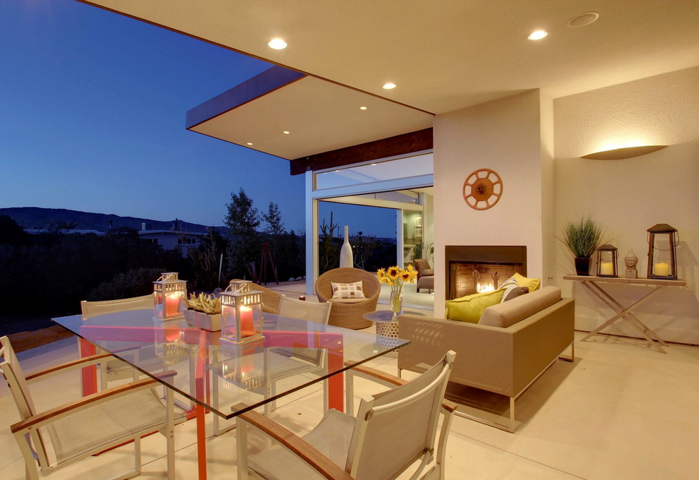This is an example of a mid-sized 1950s concrete side porch design in Los Angeles with a fire pit and a roof extension.