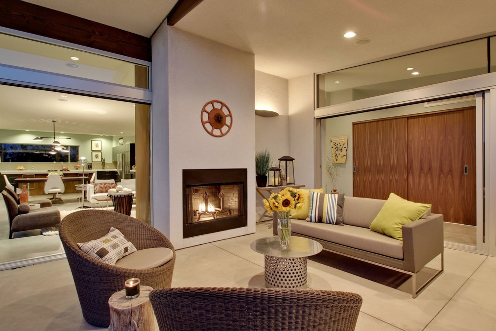 Mid-sized mid-century modern concrete side porch idea in Los Angeles with a fire pit and a roof extension