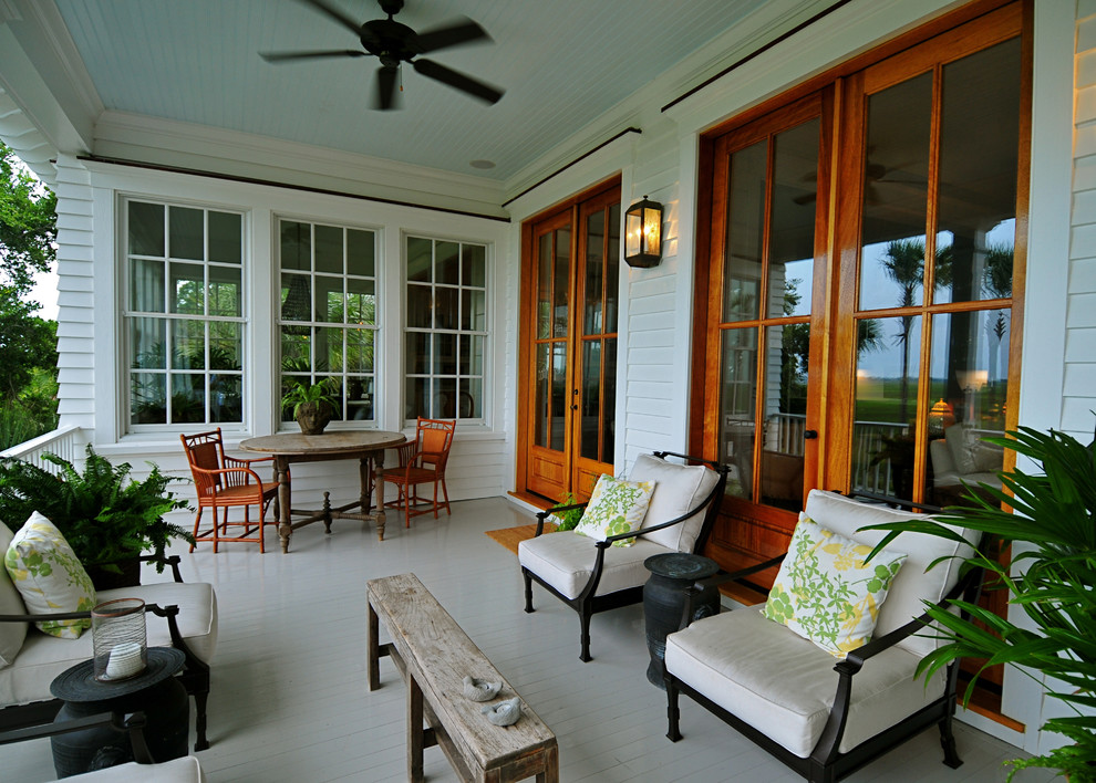 Beach style porch idea in Charleston with decking and a roof extension