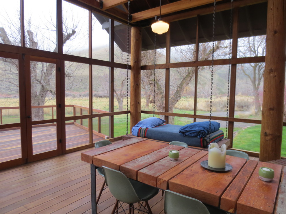 Mid-sized mountain style screened-in side porch idea in Boise with decking