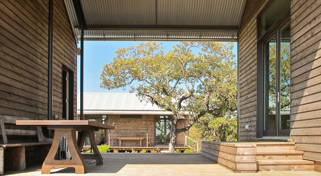Inspiration for a rustic porch remodel in Austin with a roof extension