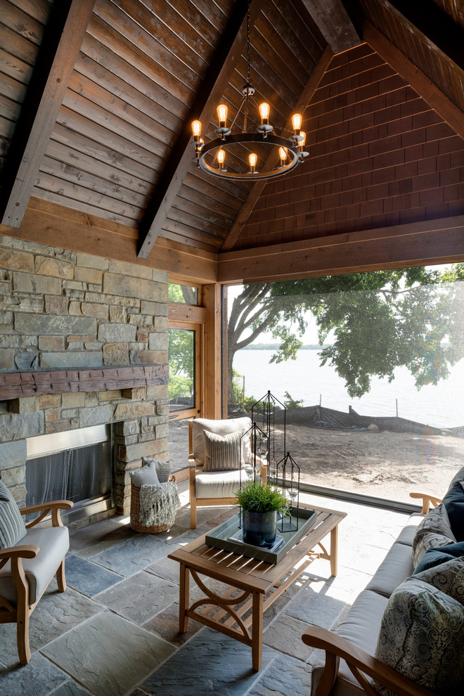 This is an example of a large rustic screened-in back porch design in Minneapolis with a roof extension.