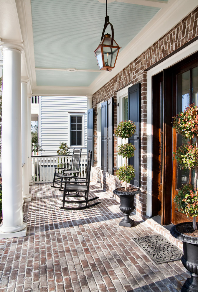 Classic brick porch idea in Charleston with a roof extension