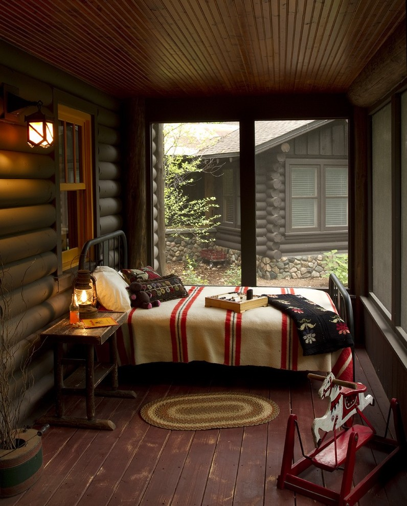 Inspiration for a rustic screened-in porch remodel in Minneapolis with decking and a roof extension