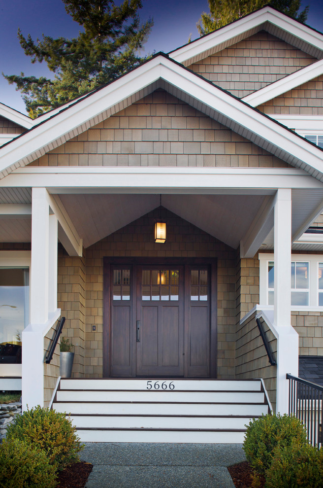 This is an example of a traditional front porch design in Vancouver with a roof extension.