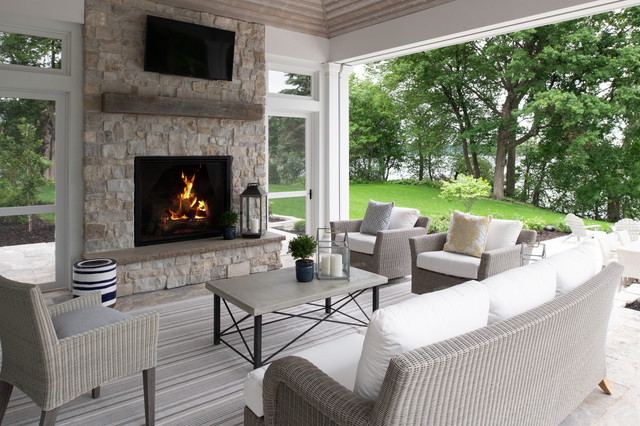 Inspiration for a mid-sized transitional stone back porch remodel in Minneapolis with a fire pit and a roof extension