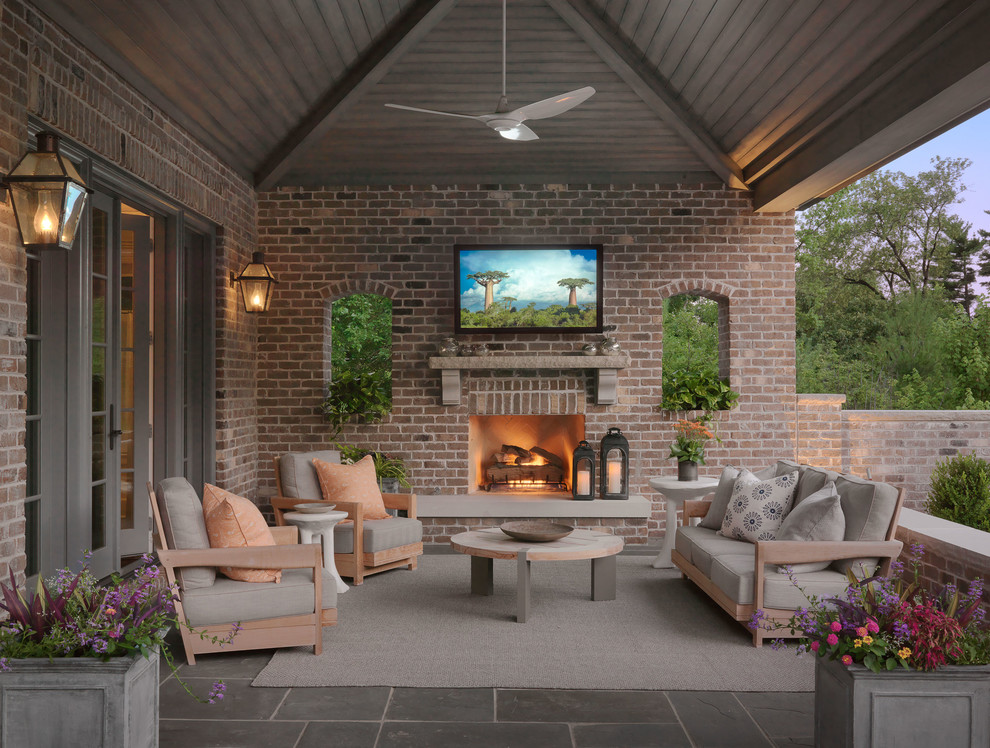 This is an example of a traditional tile porch design in Boston with a fire pit and a roof extension.