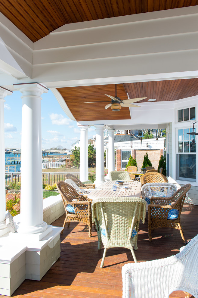 Large beach style side porch photo in New York with decking and a roof extension