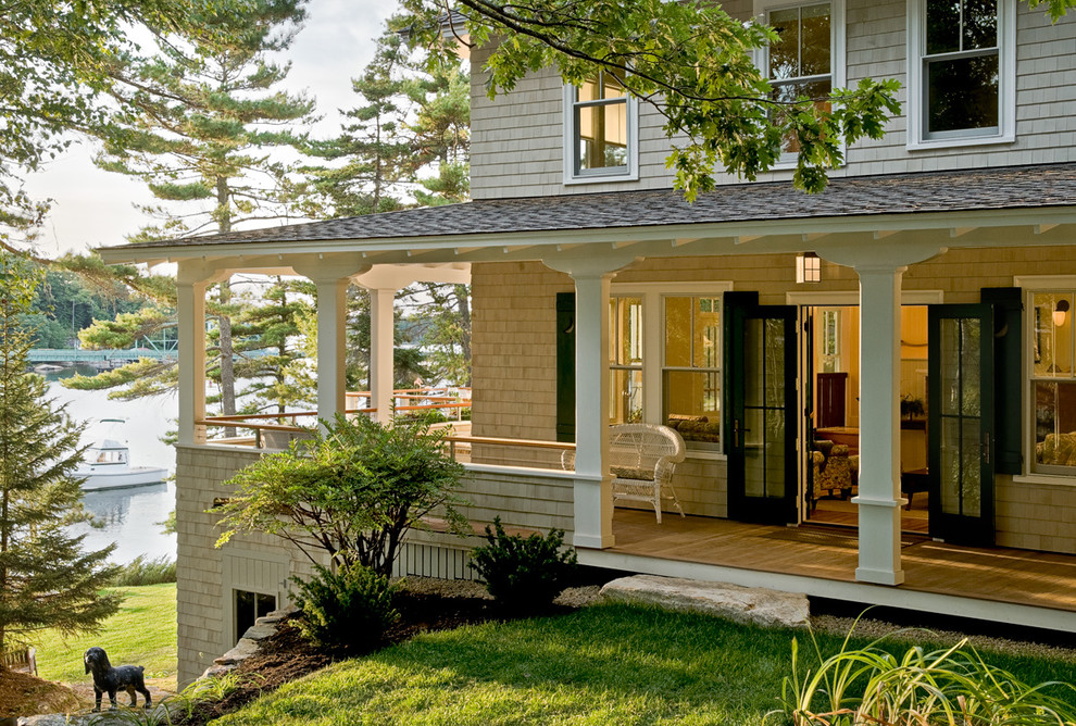 This is an example of a coastal porch design in Portland Maine with decking and a roof extension.