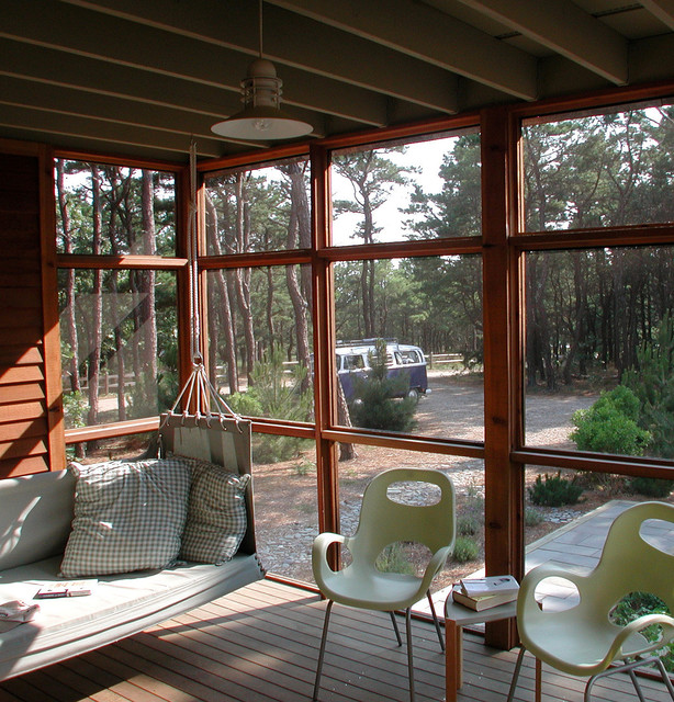 This is an example of an eclectic screened-in porch design in Boston with decking and a roof extension.