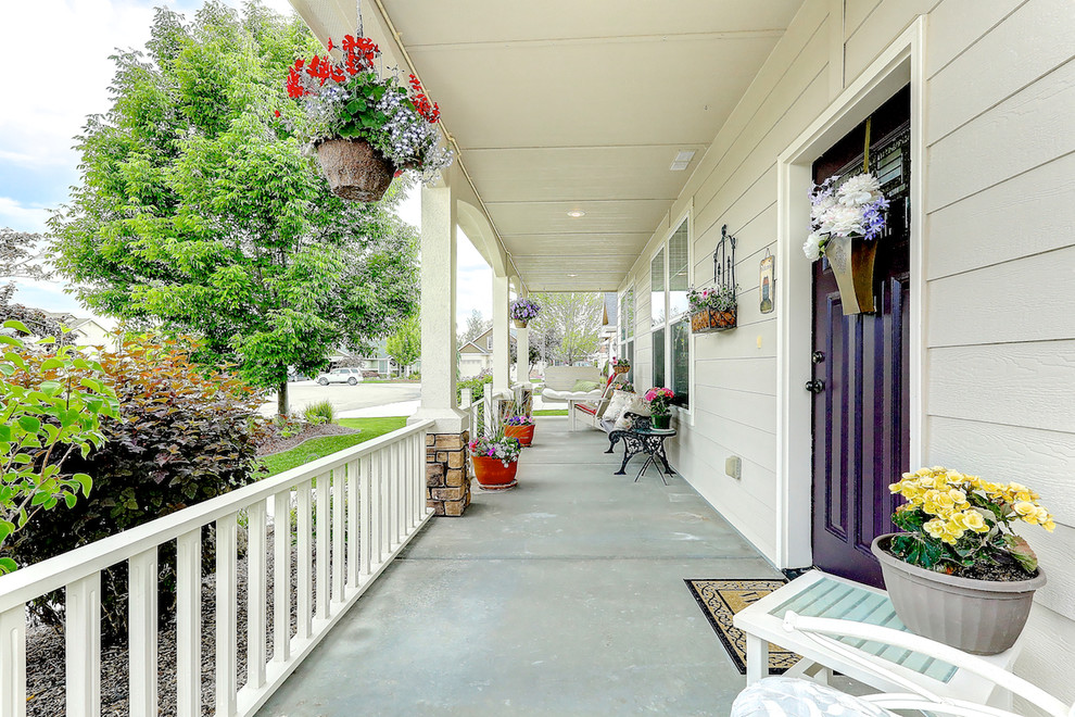 Large classic concrete front porch idea in Boise with a roof extension