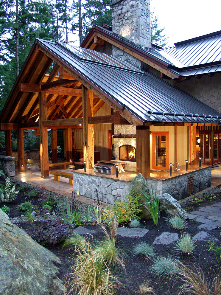 This is an example of a traditional porch design in Vancouver with a fire pit and a roof extension.