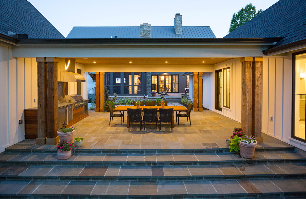 This is an example of a cottage stone porch design in Cincinnati with a roof extension.