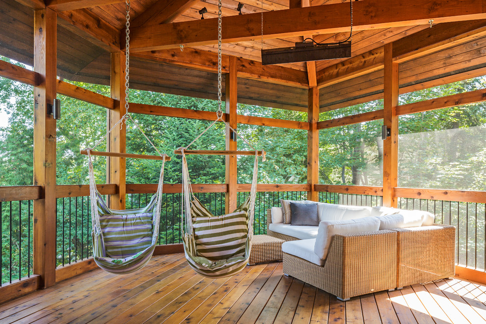 Mountain style screened-in porch idea in Montreal with a roof extension and decking